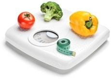 Tomaten, Brokkoli, ein Paprika und ein Maßband auf Personenwaagen