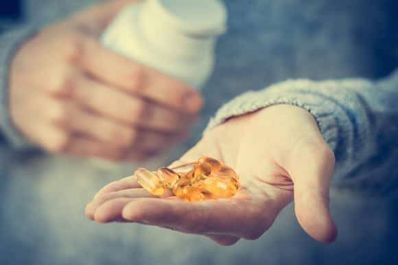 Vitamin D Kapseln in der Hand des Menschen