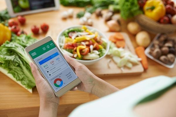 Frau, die Kalorien und verbrauchte Makronährstoffe berechnet