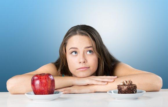 Frau, die zwischen Apfel und Kuchen entscheidet