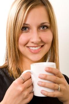 Frau, die Kaffee trinkt, lächelt