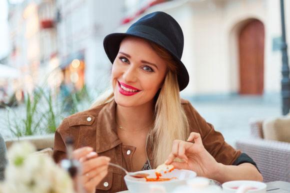 Frau, die Tomatensuppe am Restaurant im Freien isst