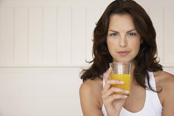 Frau, die ein Glas Orangensaft hält und skeptisch aussieht