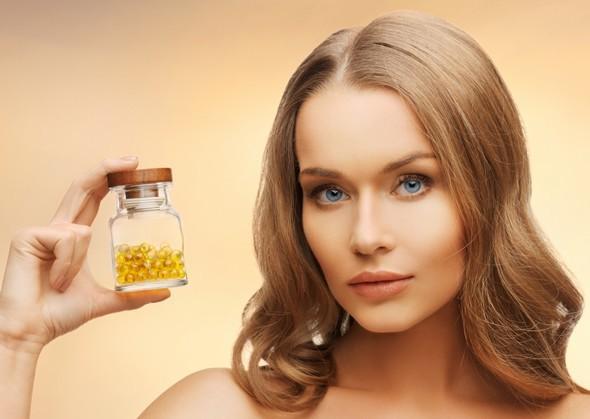 Frau, die eine Flasche ölgefüllte Kapseln hält