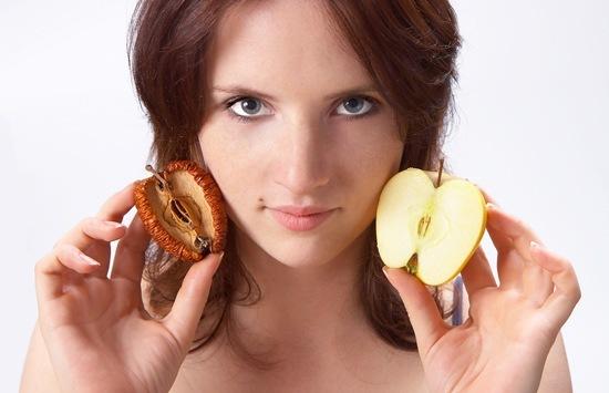 Frau, die frischen und getrockneten Apfel hält