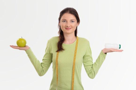 Frau, die Probiotikum und Apfel hält