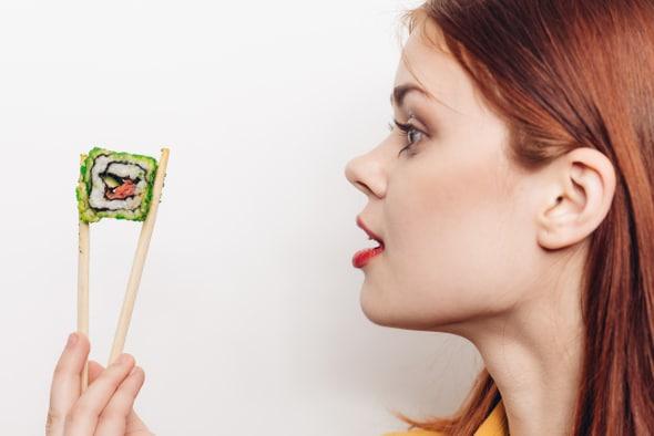 Frau, die Stück Sushi in Essstäbchen betrachtet