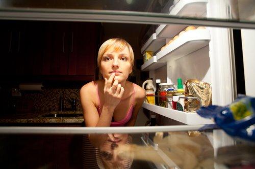 Frau, die in einen Kühlschrank schaut