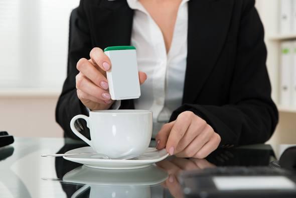 Frau, die Süßstoff in ihren Kaffee setzt