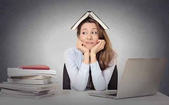 Frau, die am Computer mit Büchern sitzt