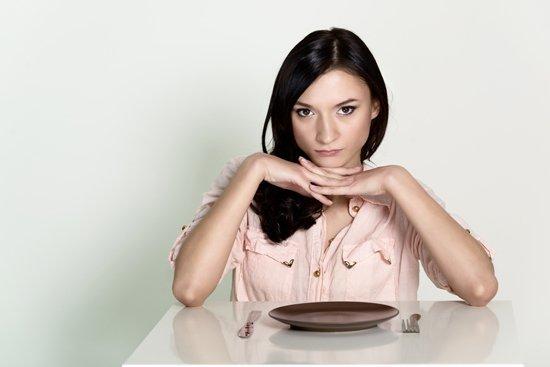 Frau, die mit einem leeren Teller sitzt