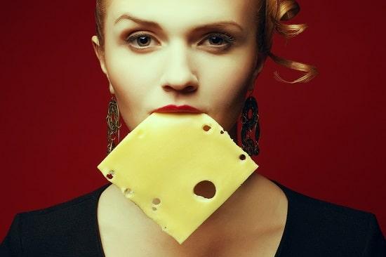 Frau mit einer Scheibe Käse im Mund