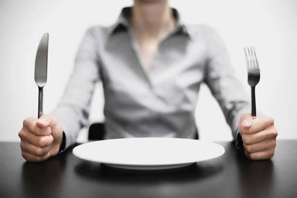 Frau mit einer leeren Platte vor ihr, die eine Gabel und ein Messer hält