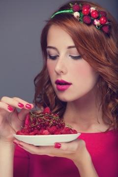 Frau mit roten Haaren, die Beeren essen