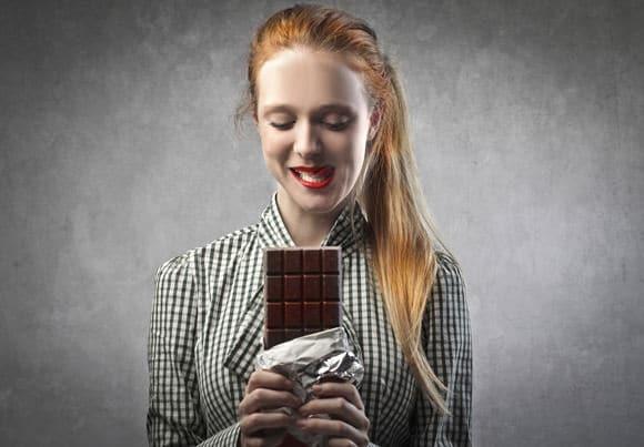 Frau mit dem roten Haar, das einen Schokoriegel hält