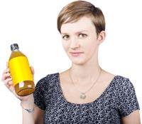 Frau mit dem kurzen Haar, das eine Flasche Apfelessig hält