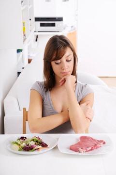 Frau, die sich über Salat und Fleisch wundert