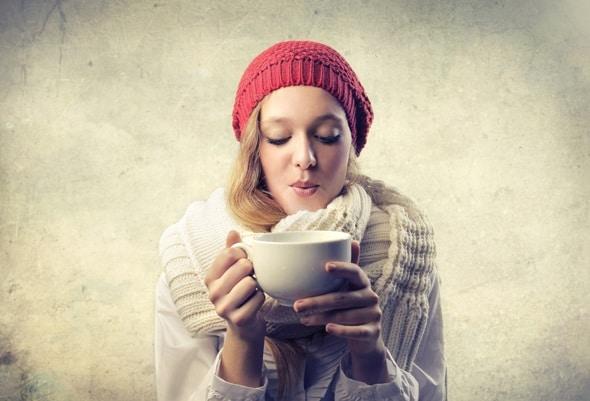 Junge Blondine, die heißen Tee trinkt