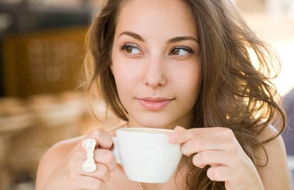 Junge Brünette, die Tasse Kaffee genießt