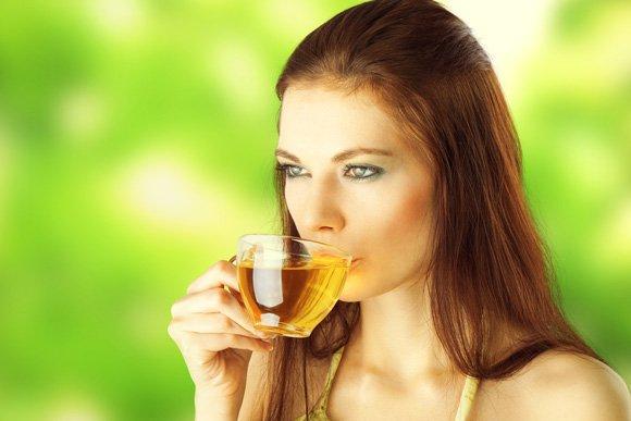Junge Frau, die grünen Tee trinkt