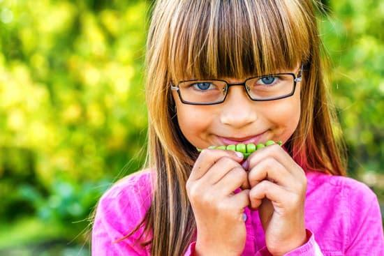 Junges Mädchen, das Erbsen isst