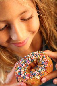 Junges Mädchen, das Donut betrachtet