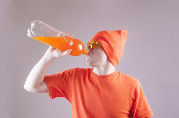 Junger Mann, der Soda von einer Flasche trinkt