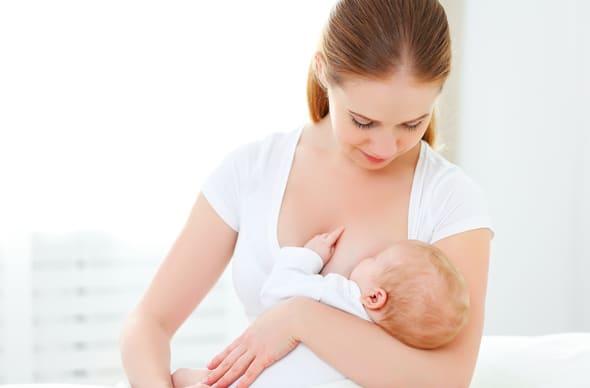 Stillendes Baby der jungen Frau