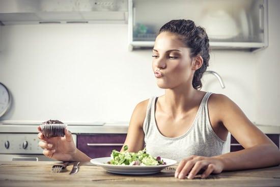 Junge Frau, die entscheidet, ob sie einen Salat oder einen Muffin isst
