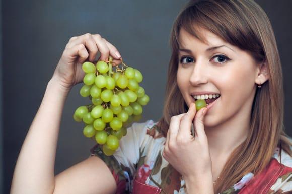 Junge Frau, die grüne Trauben isst
