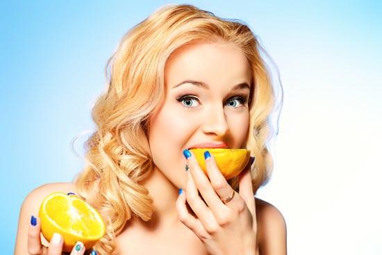 Junge Frau, die Orange isst