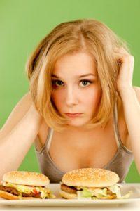 Junge Frau fühlt sich schlecht über das Essen von Junk Food