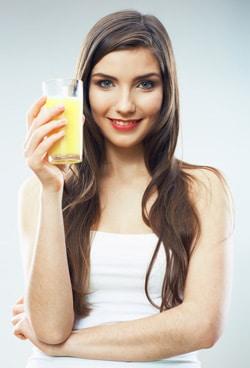 Junge Frau, die ein Glas Orangensaft hält