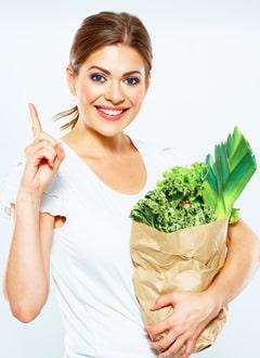 Junge Frau, die eine Papiertüte mit Gemüse hält