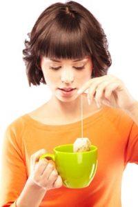 Junge Frau, die eine Tasse grünen Tee macht
