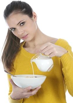 Junge Frau, die Milch in eine Schüssel gießt