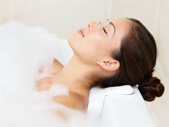 Junge Frau, die sich in einem Bad entspannt