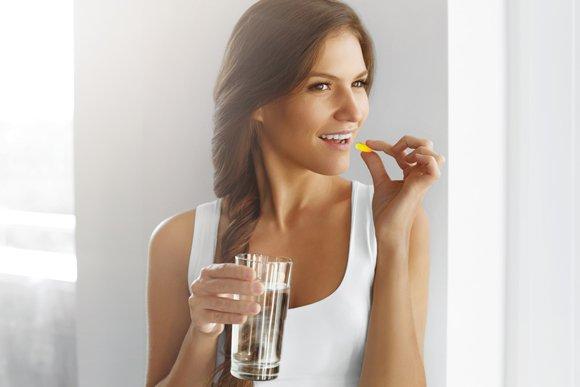 Junge Frau mit Fischöl und Glas Wasser, horizontal