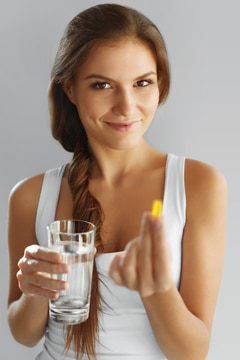 Junge Frau mit Fischöl und Glas Wasser