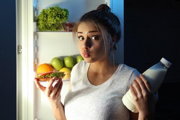 Junge Frau, die sich fragt, ob sie vor dem Schlafengehen etwas essen soll